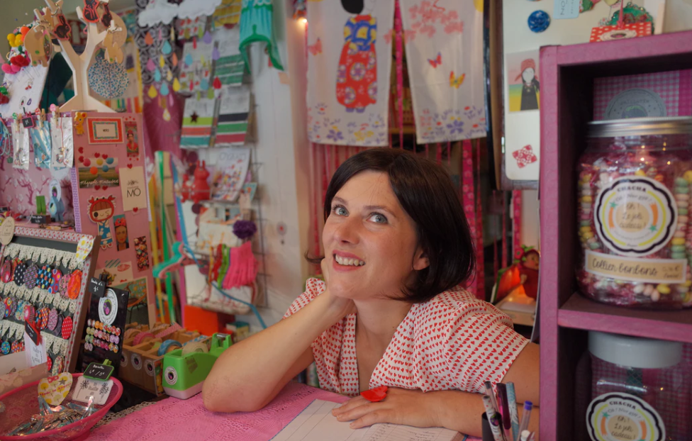 woman deciding between Silhoutte and Cricut machines in a craft shop surrounded by projects